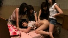 Japanese cutie gets tied up so her lusty girlfriends can stroke her private parts