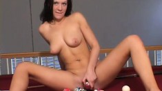 Rhonda sits on a pool table surrounded by balls and plays with herself