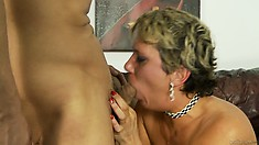 The busty blonde gets fucked hard on the sofa and receives his cum on her hairy twat