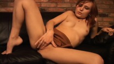 Sexy redhead sits on her sofa and uses her fingers to rub one out
